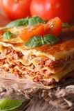 Tasty lasagna with basil and tomatoes on an old table, vertical Royalty Free Stock Photography