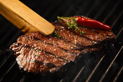 Tasty lean rump steak sizzling on a BBQ fire. Seasoned with a whole red hot chili pepper and sprig of fresh rosemary in a close up view being lifted off the royalty free stock image