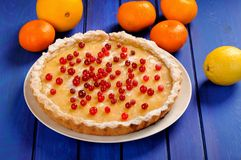 Tasty lemon pie decorated with fresh cranberries and whole orang Stock Photography