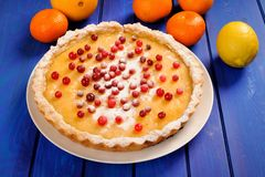 Tasty lemon pie decorated with fresh cranberries and whole orang Royalty Free Stock Photography