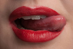Tasty lips. Detail of young female licking her red lips Stock Image
