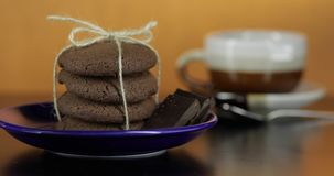 Tasty looking chocolate cookie on a blue plate on dark surface. Warm background. Tasty looking chocolate cookie on a blue plate on dark surface. Vintage warm stock footage