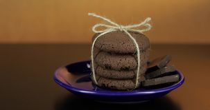Tasty looking chocolate cookie on a blue plate on dark surface. Warm background. Tasty looking chocolate cookie on a blue plate on dark surface. Vintage warm stock video footage
