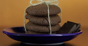 Tasty looking chocolate cookie on a blue plate on dark surface. Warm background. Tasty looking chocolate cookie on a blue plate on dark surface. Vintage warm stock video