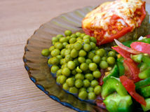 Tasty Lunch. Closeup plate with fresh vegetables, peas and cutlets with cheese Stock Photography