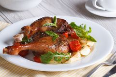 Tasty lunch: fried duck legs, with apples, tomatoes and herbs Royalty Free Stock Images