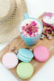 Tasty macaron cookies with a blue cup of cappuccino with roses petals and straw hat on white table. Royalty Free Stock Photos