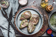 Tasty marinating meat steaks with herbs and spices for grill or barbecue on kitchen table with Stainless steel on rustic kitchen t Royalty Free Stock Photography