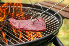 Tasty meat on barbecue grill with fire flames outdoors. Closeup stock images