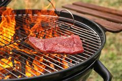 Tasty meat on barbecue grill with fire flames outdoors. Closeup royalty free stock image