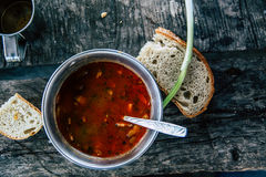 Tasty meat soup with fresh bread on old wooden table.  Stock Image