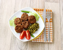 Tasty meatballs, green peas and tomatoes on plate Stock Images