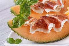 Tasty melon with ham and basil close-up  horizontal Stock Photos