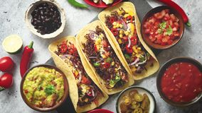 Tasty Mexican meat tacos served with various vegetables and salsa. With sides in ceramic bowls around. Top view composition stock footage
