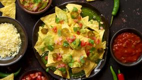Tasty mexican nachos chips served on ceramic plate. With cheese, hot peppers, tomatoes, limes, salsa and guacamole. Placed on dark rusty table stock video