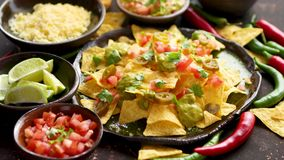 Tasty mexican nachos chips served on ceramic plate. With cheese, hot peppers, tomatoes, limes, salsa and guacamole. Placed on dark rusty table stock video footage