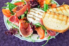 Tasty mixed salad dish with grilled camembert cheese, prosciutto ham, organic tomato and fresh green leaves. Healthy dilicious. Meal. Isolated on black stock image