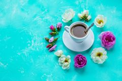 Tasty morning concept. Flat lay of cup of freshly brewed coffee surrounded with white and pink roses flowers and petals royalty free stock photos