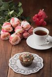 Tasty muffin and a cup of hot tea with roses Royalty Free Stock Images