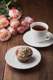Tasty muffin and a cup of hot tea with roses Royalty Free Stock Image