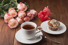 Tasty muffin and a cup of hot tea with roses Stock Photos