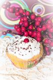 Creamy muffin. Dusted with white icing and chocolate chips. With red berries on top on a white lacy napkin and gold beads Stock Photos