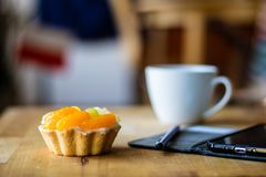 Tasty muffin with fruit on a wooden kitchen table. Coffee and phone with notes. Stock Photos