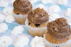 Tasty muffins with chocolate cream decorated with sugar candies in a blue checkered tablecloth  and meringue. Sweet pastries Stock Image
