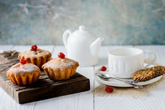 Tasty muffins with raisins and dried cherry. On a white wooden table Royalty Free Stock Images