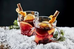 Tasty mulled red wine with orange and cinnamon. Tasty mulled red wine, or Gluhwein, with orange and cinnamon served in glasses on a bed of winter snow to Royalty Free Stock Photography