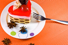 Tasty multy layer cake with chocolate decorations. Tasty and colorful multy layer cake with chocolate decorations and red jelly. Cake is placed on the white Royalty Free Stock Images