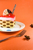 Tasty multy layer cake with chocolate decorations. Tasty and colorful multy layer cake with chocolate decorations and red jelly. Cake is placed on the white Stock Photography