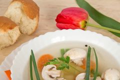 Tasty mushroom soup, slices of bread and red tulip Royalty Free Stock Photography