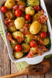 Tasty new potatoes baked with bacon, herbs and tomatoes macro in Royalty Free Stock Photo