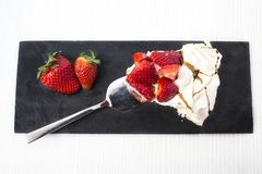 Tasty and nice piece of meringue pie with red strawberry ornament on a black slate plate. Piece of meringue pie with red strawberry garnished in half and spoon Stock Photos