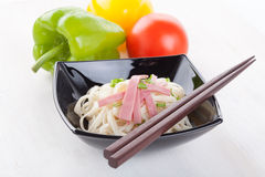 Tasty noodles with ham green onions in a beautiful black bowl on a white wooden background. Pepper and tomatoes. Royalty Free Stock Images