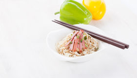 Tasty noodles with ham green onions in a beautiful white bowl on a white wooden background. Peppers and tomatoes. Stock Images
