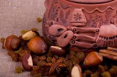 Tasty nuts and clay pot Stock Photos