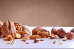 Tasty nuts in shell and shelled on a white table Stock Photography