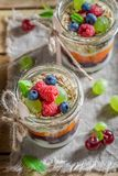 Tasty oat flakes with fresh fruits and yoghurt in jar. On wooden tray stock photo