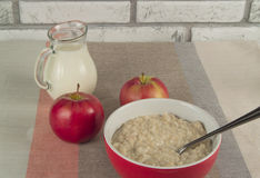 Tasty oatmeal with apples and  jug of milk. Healthy nutrition Stock Photography