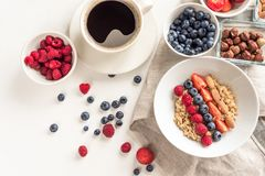 Good morning - healthy breakfast background with oatmeal coffee, berries, egg, nuts. White wooden food background, stock photos