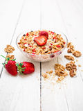 Tasty oatmeal porridge with strawberries, nuts and muesli on wood table. Diet breakfast. Tasty oatmeal porridge with strawberries, nuts and muesli on wood table Stock Photography