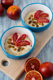 Tasty oatmeal with sicilian orange slices and raisins on blue bowls Royalty Free Stock Photo