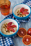 Tasty oatmeal with sicilian orange slices and raisins on blue bowls Stock Photos