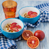 Tasty oatmeal with sicilian orange slices and raisins on blue bowls Royalty Free Stock Photography