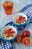 Tasty oatmeal with sicilian orange slices and raisins on blue bowls. On wooden background Stock Photo