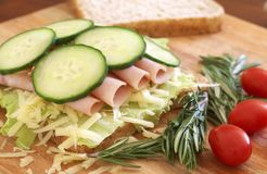 Tasty open sandwich on wholewheat bread. Tasty open sandwich with green lettuce, grated cheese, smoked ham and cucumber on wholewheat bread with rosemary and Royalty Free Stock Photography