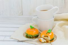 Tasty orange mousse cakes and cup of coffee on white wooden tray Royalty Free Stock Photography