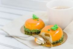 Tasty orange mousse cakes and cup of coffee on white wooden tray Stock Photography